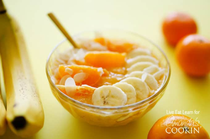 A close up of an almond orange smoothie bowl topped with mandarine oranges and sliced banana.