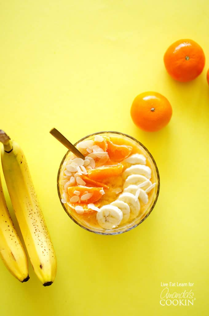 An overhead of an almond orange smoothie bowl topped with mandarine oranges and sliced banana.