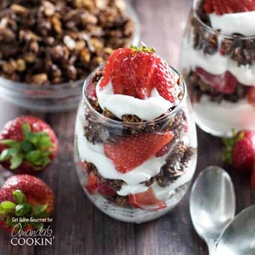 A close up photo of breakfast parfaits with strawberries and dark chocolate granola.