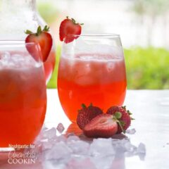 Two short glasses filled with strawberry lemonade served with sliced strawberries on the rim of the glass and on the side.