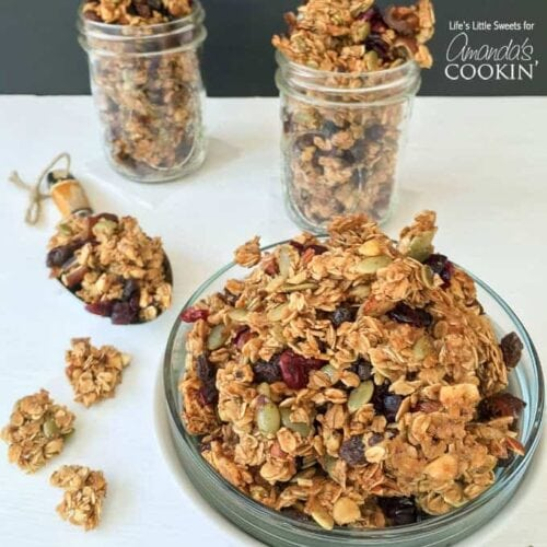 A photo of a plate of autumn harvest fruit and nut granola and two filled mason jars in the background.