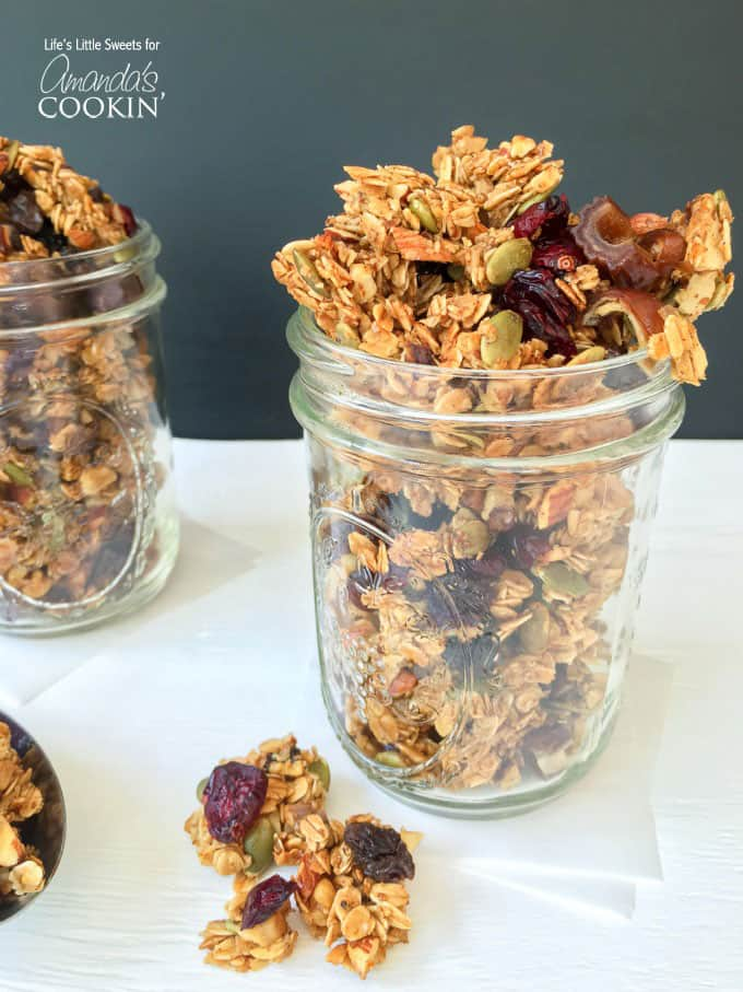 A close up photo of autumn harvest fruit and nut granola in a mason jar.