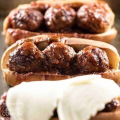 A close up photo of three slow cooker BBQ meatball subs, one topped with provolone cheese.