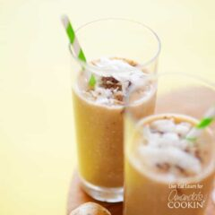 Two tall clear glasses filled with a cozy coconut smoothie and served with a green and white striped straw.