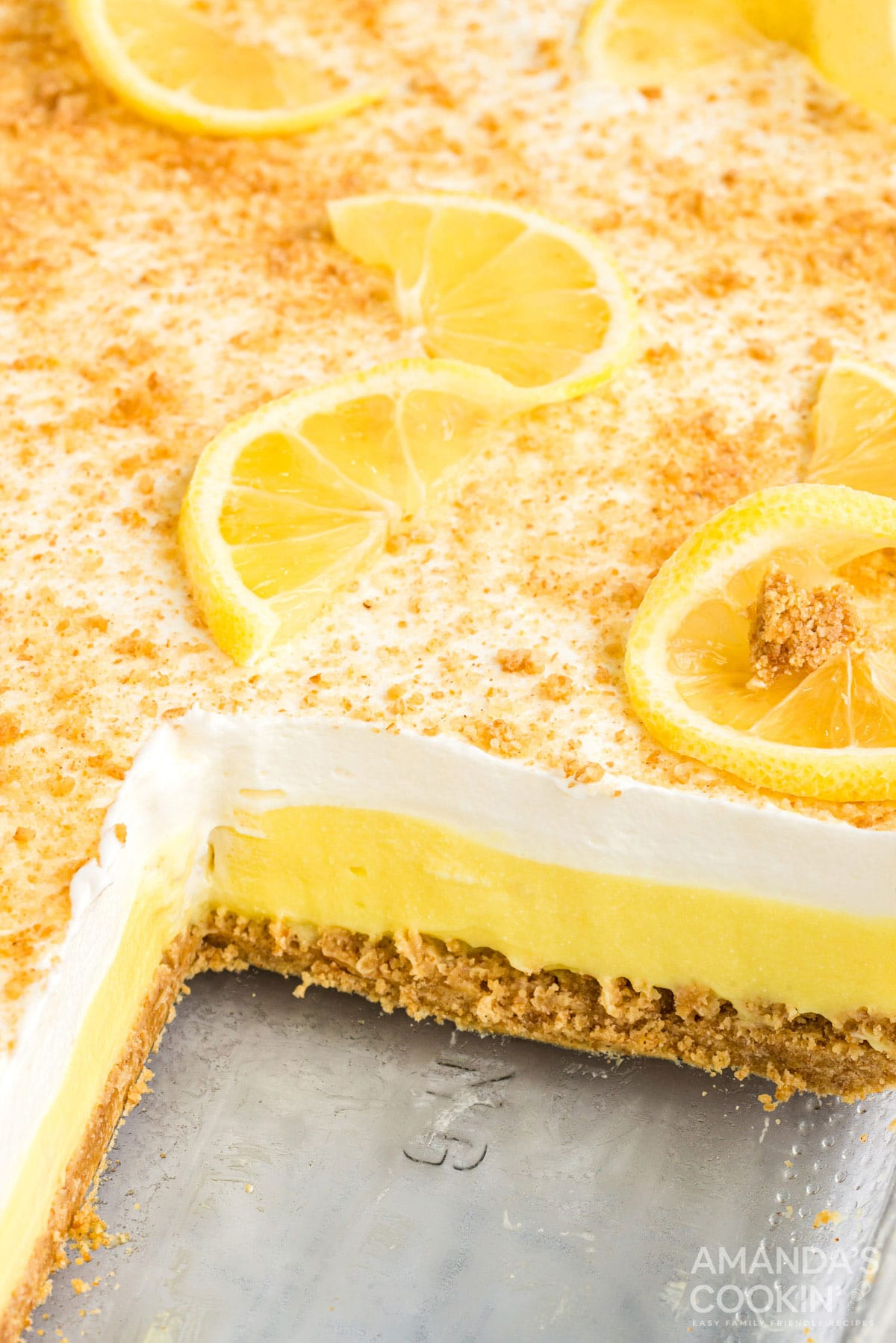 layered lemon dessert in a pan with a slice removed