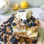A square of blueberry lemon crumble no bake cheesecake on a spatula.