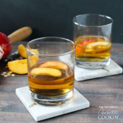 Two short clear glasses filled with peach pie cocktail with two peach slices floating on top.