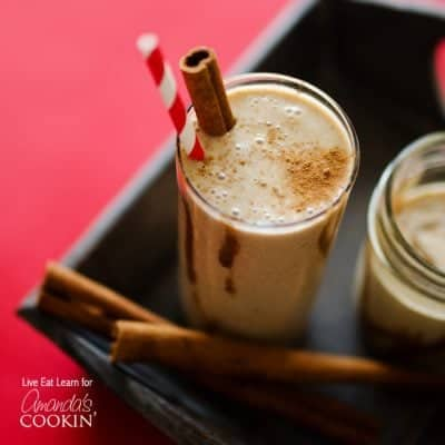 A tall clear glass filled with a cinnamon bun smoothie and served with a cinnamon stick and a red stripped straw.