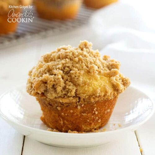 A close up of a cinnamon streusel muffin in a white bowl.