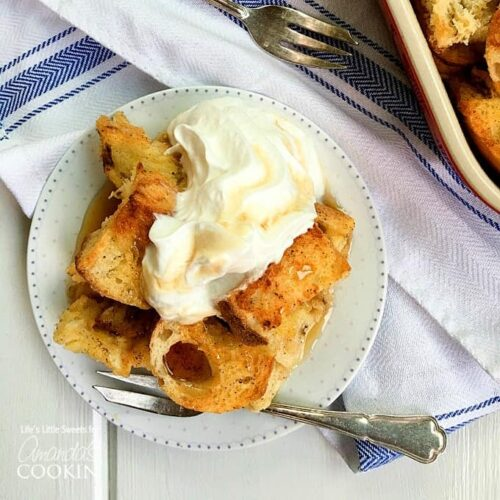 An overhead of french toast casserole on a white plate topped with vanilla whipped cream.