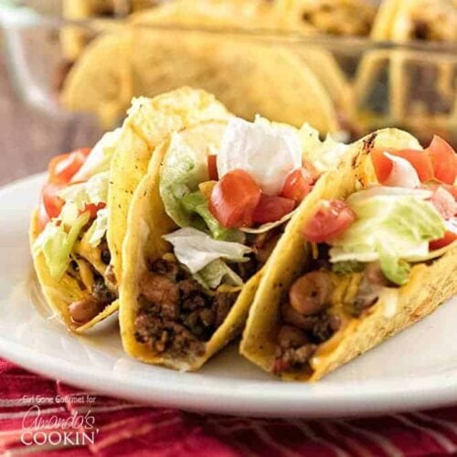 Three hard shell beef and bean oven tacos resting on a white plate topped with lettuce, tomatoes and sour cream.
