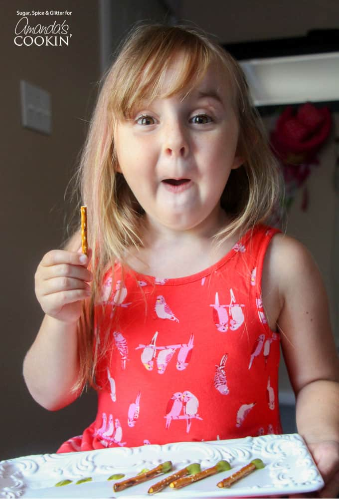 A little girl holding a pretzel stick.