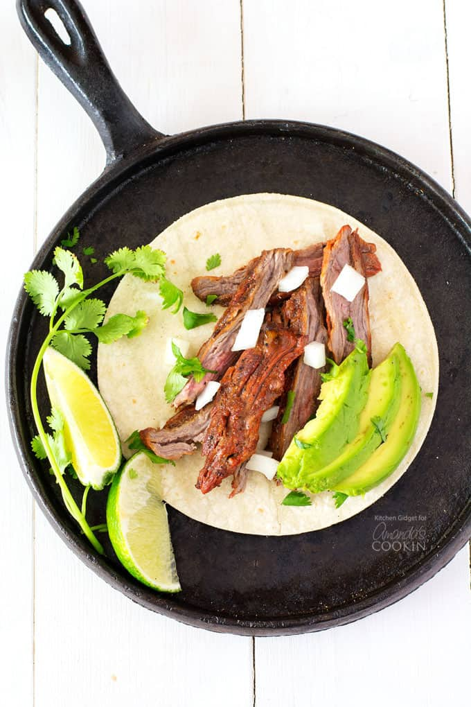 carne asada on skillet with avocado and lime