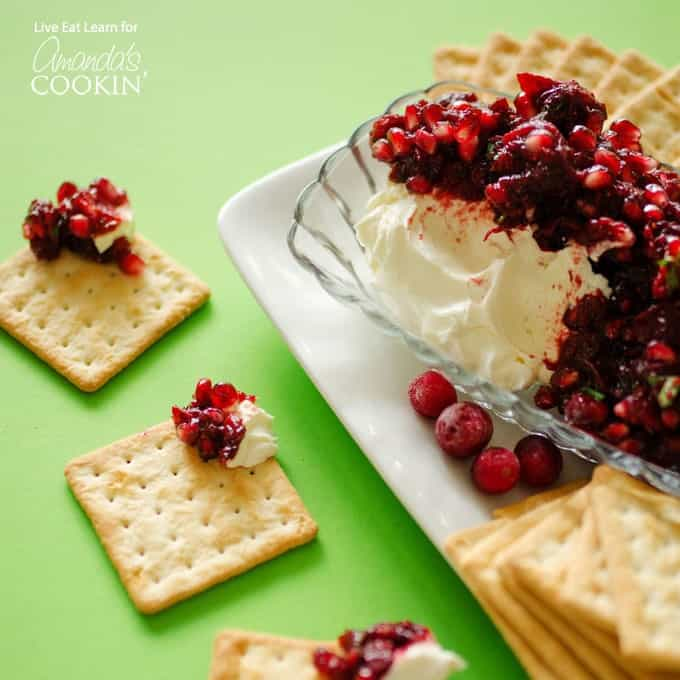 Cranberry salsa spooned over cream cheese in a glass dish with cracker squares surrounding.