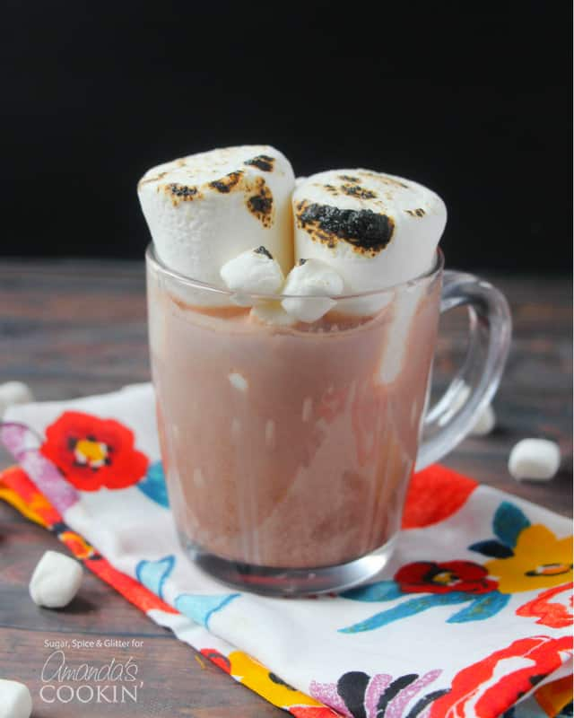 A clear mug filled with a hot chocolate cocktail and two roasted marshmallows on top.