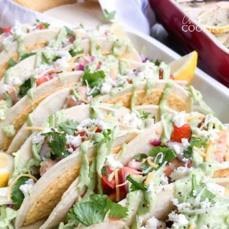 These Salmon Tacos are topped with homemade salsa and avocado sauce and accented with fresh cilantro. These tasty fish tacos are perfect for a crowd!