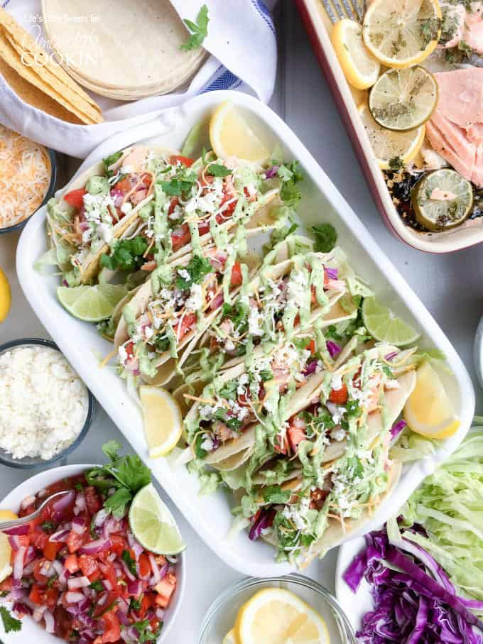 An overhead photo of salmon tacos resting in a casserole dish with lemon and lime wedges on the side.