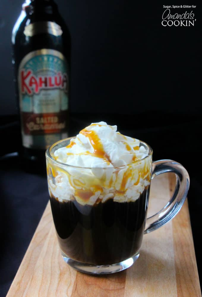 A salted caramel coffee cocktail in a clear mug with whipped cream and drizzled caramel on top.