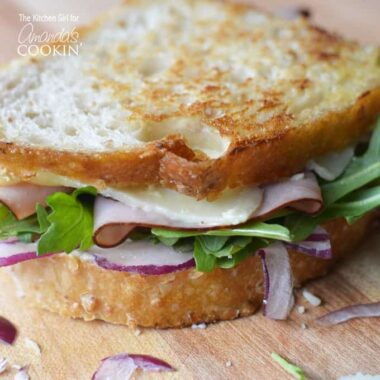 A close up of a toasted cheddar, ham and arugula sandwich.