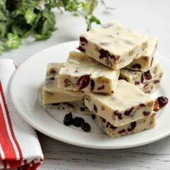 Squares of white chocolate cranberry fudge on a white plate.