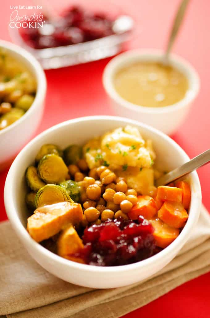 A close up of a Thanksgiving leftovers bowl filled with chickpeas, carrots, brussles sprouts, sweet potatoes, mashed potatoes, cranberry sauce and gravy.
