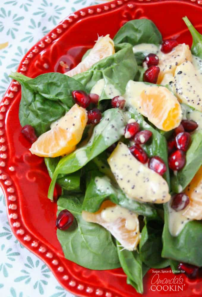 A close up of a pomegranate clementine spinach salad on a red plate.
