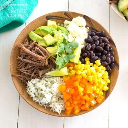 An overhead of a brown bowl filled with white rice, bell pepper, corn, black beans, crumbled queso fresco, avocado, lime and cooked beef.