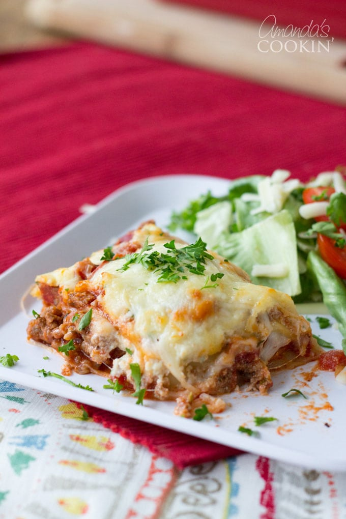 slice of lasagna on a plate with salad