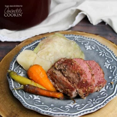 A blue plate with cooked corned beef, cabbage and carrots.