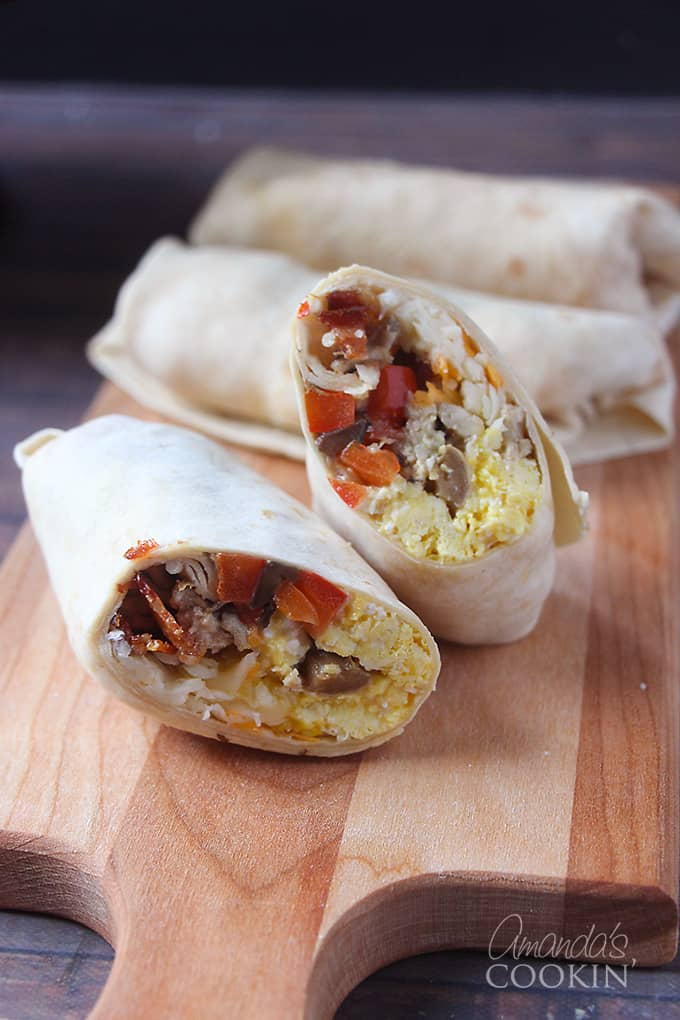 A breakfast burrito cut in half with one side stacked on the other with whole burritos in the background all resting on a wooden cutting board.