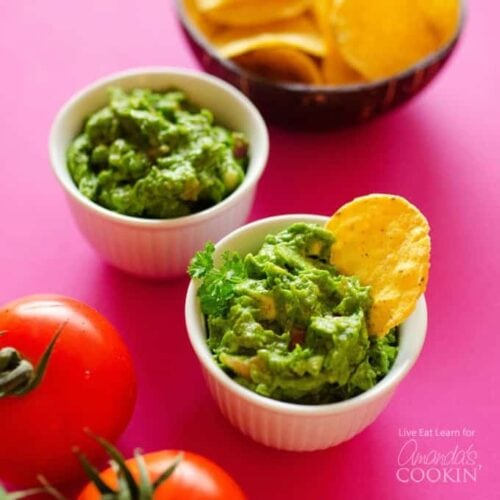 Two white bowls of guacamole with a bowl of chips in the background and two tomatoes.