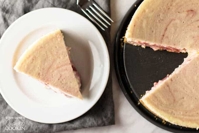 A slice of strawberry swirled cheesecake on a white plate sitting next to the entire baked cheesecake.