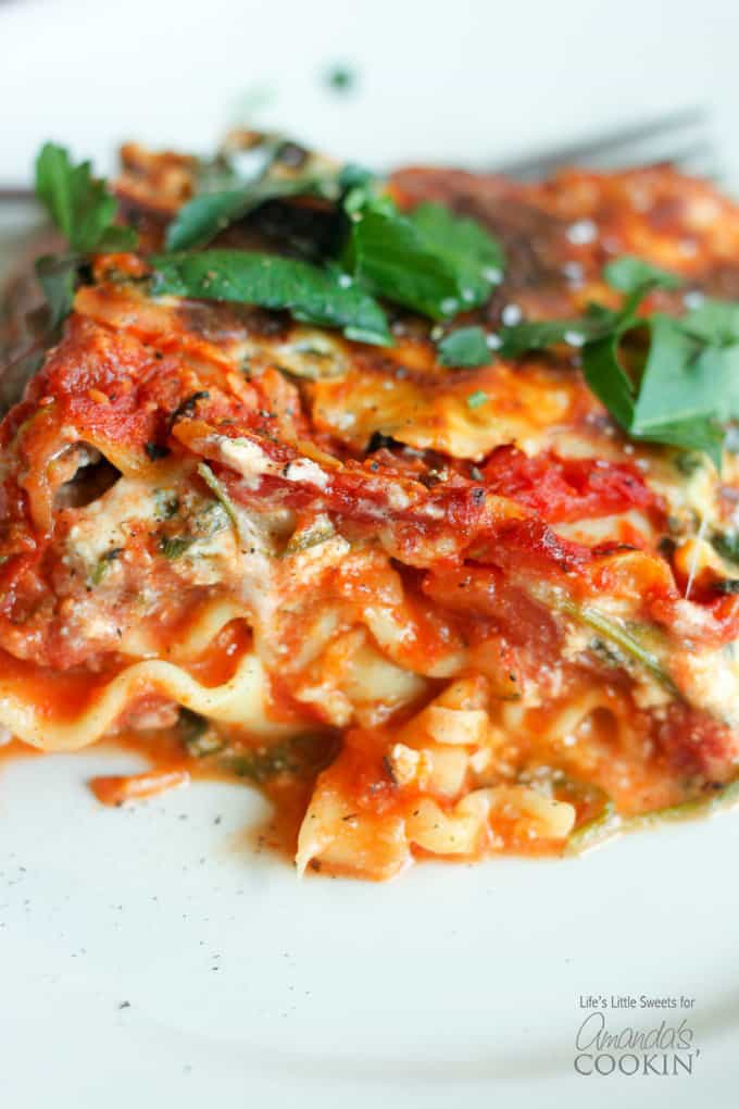 A close up of veggie lasagna on a white plate.