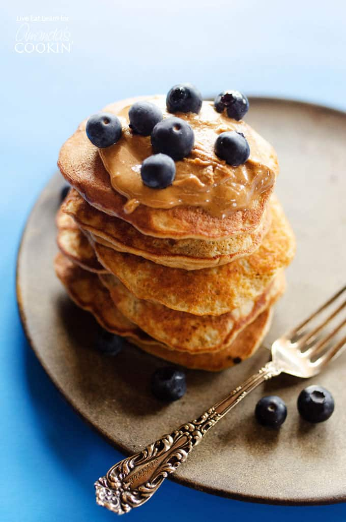 stack of pancakes with blueberries on top on a brown plate