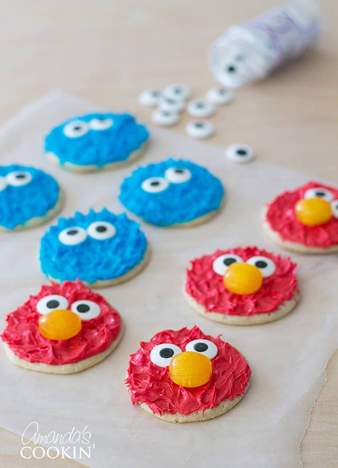 elmo and cookie monster decorated cookies on parchment