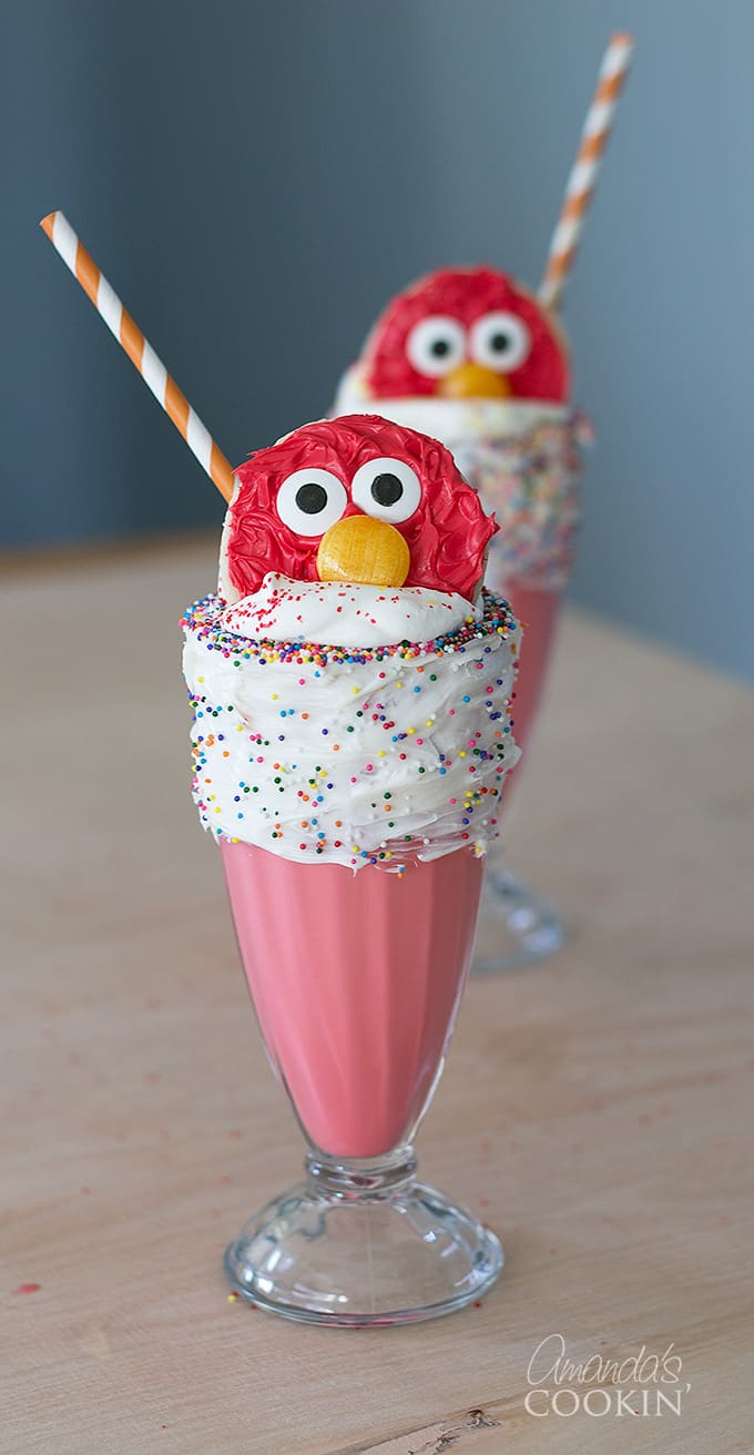 Elmo Freakshakes in a glass with vanilla frosted rim and elmo cookie.
