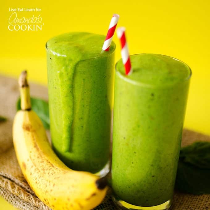 two green smoothies with a banana and red paper straws