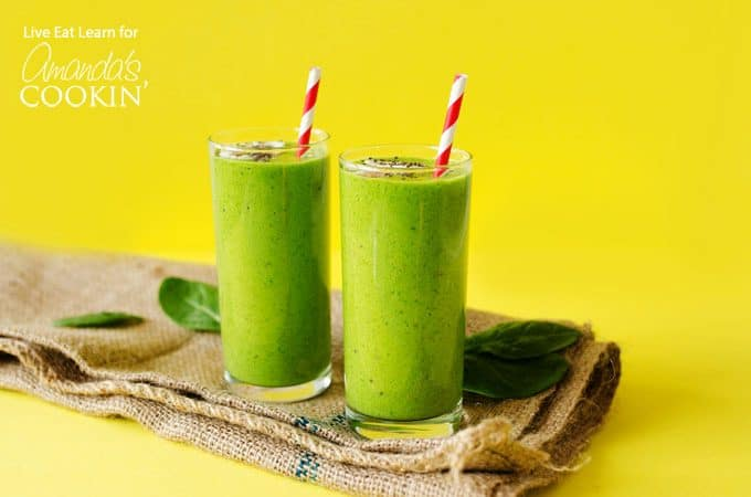 Green smoothies on yellow background with paper straws