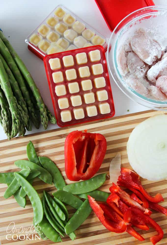 """Wash and dry the vegetables well. Chop the asparagus in 3"""" pieces, remove any rough ends from the snap peas, and slice the red peppers."""