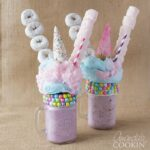 two purple milkshakes with donuts and marshmallows