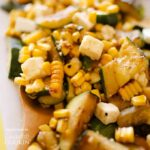 wooden spoon in corn zucchini salad