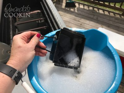 dropping grease catcher from grill into soapy water to soak