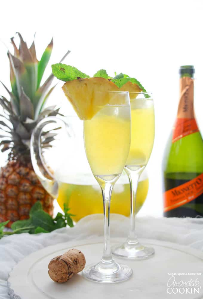 flutes with pineapple prosecco punch and pineapple garnish