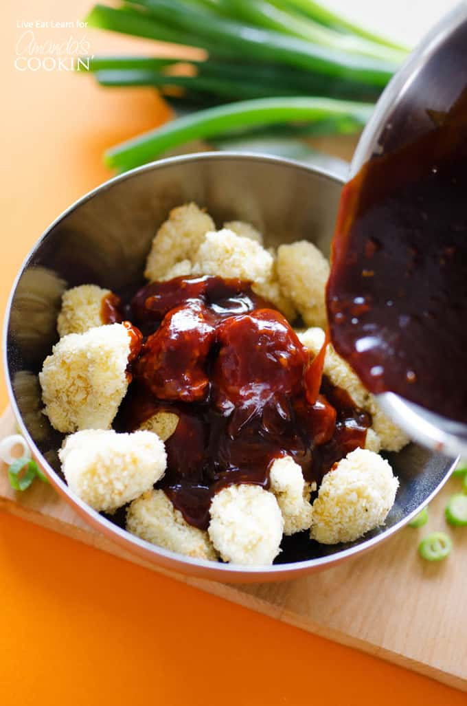 Mixing sauce with breaded cauliflower