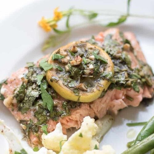 salmon on a plate with lemon garnish