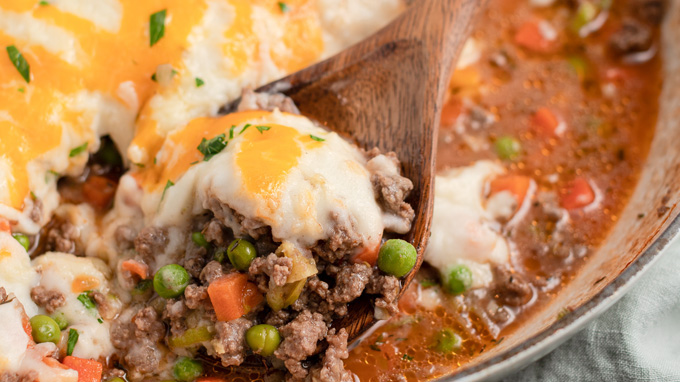 close up shepherds pie in a wooden spoon