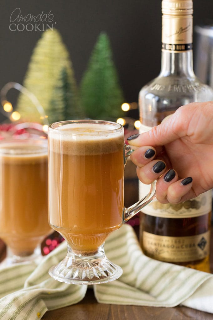 woman's hand picking up glass of hot buttered rum
