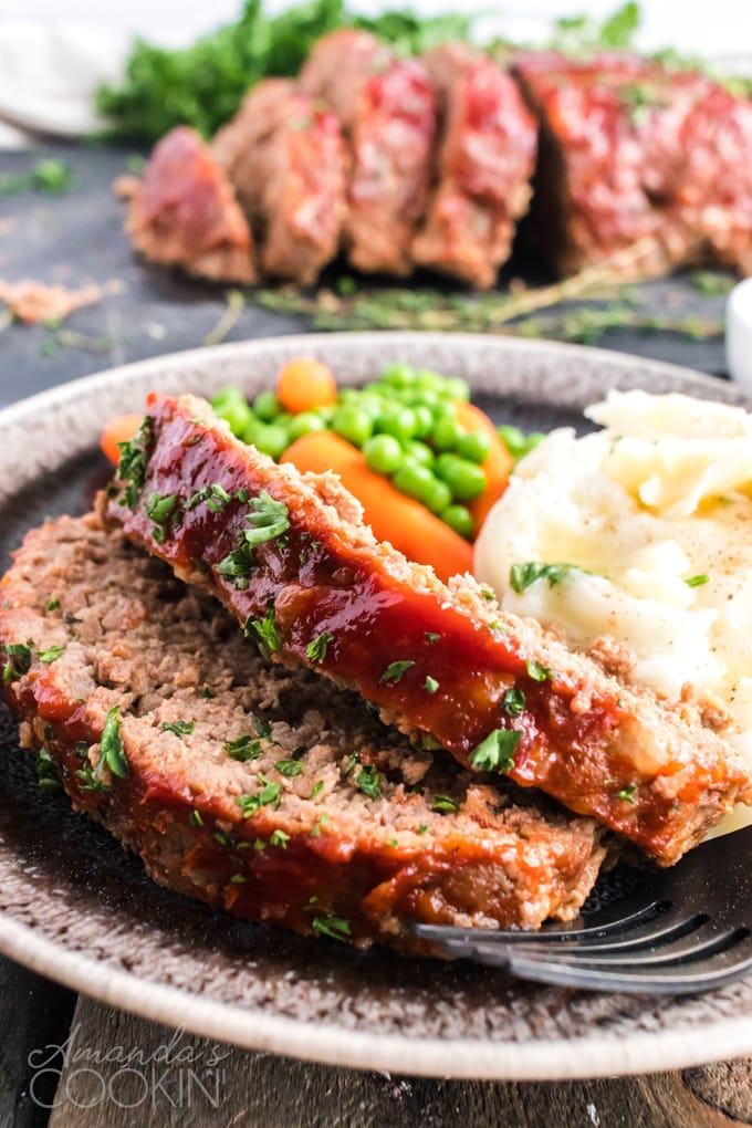 2 slices of meatloaf on a plate with mashed potatoes