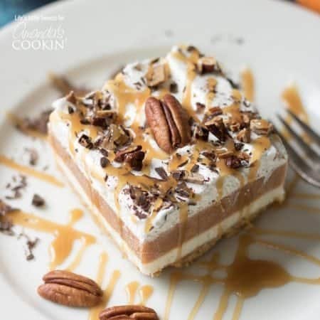 This Pumpkin Lasagna has a graham cracker crust, a sweet cream cheese layer, pumpkin spice Jello pudding, Cool Whip and topped with toasted, chopped pecans.