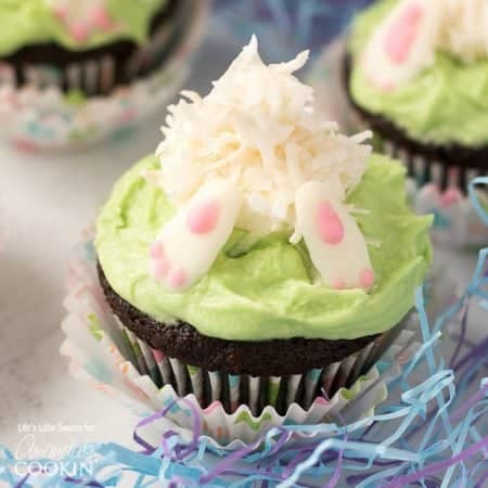 """These Bunny Butt Cupcakes are the perfect Easter and Springtime-themed cupcakes! They have a delicious and moist chocolate cupcake base with a marshmallow and coconut flake bunny diving into buttercream """"grass"""" frosting with white chocolate feet."""